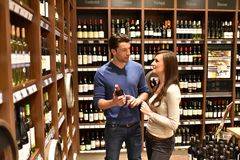 Young lucky couple shopping for wine in the supermarket. Closeup Royalty Free Stock Photo