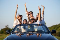 Young lucky girls and boys in sunglasses are sitting in a black cabriolet on the road holding their hands up and making stock image