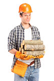 A young lumberjack holding a firewoods Royalty Free Stock Images