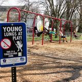 `Young Lungs at Play` sign on playground. A `Young Lungs at Play` sign at Lititz Spring park, while kids swing in the background.  Taken April 13th, 2019 around stock photos