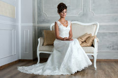 Young luxurious brunette bride sitting on vintage sofa Royalty Free Stock Image