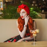 Young luxury woman with long hair, pale skin and in rose summer dress in cafe. Beautiful elegant redhead model eat ice cream in ca. Fe. Fashion style. Stylish stock photos
