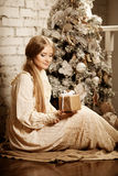 Young luxuy vintage woman near Christmas tree with gift. Beautif Stock Photos