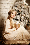 Young luxuy vintage woman near Christmas tree with gift. Beautif Stock Photography