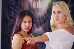 Young mad american blonde woman, exhorting to a latin woman to leave the country, using her arm and pointing somewhere. Young mad american blonde woman Royalty Free Stock Image