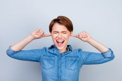 Young mad girl is screaming with closed eyes and ears. She doesn. `t want to hear anyone Royalty Free Stock Photo