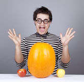 The young mad men try to eat apples and pumpkin. Royalty Free Stock Photo