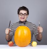 The young mad men try to eat apples and pumpkin. Royalty Free Stock Images