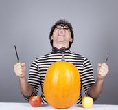The young mad men try to eat apples and pumpkin. Royalty Free Stock Photography