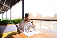 Handsome illustrator watching magazine pictures at table. Young magazine illustrator watching catalog with photos at cafe table. Handsome male person sitting Stock Image
