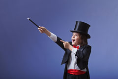 Young magician performing with a magic wand stock photo