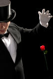 Young magician performing red rose Royalty Free Stock Photo