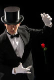 Young magician performing red rose Stock Photo