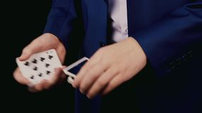 Young magician show a trick with cards stock footage