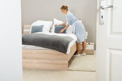 Young maid arranging pillow on bed Royalty Free Stock Images