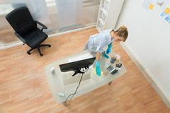 Young maid cleaning desk Royalty Free Stock Images