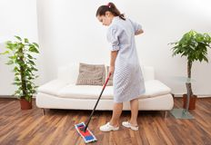 Young maid cleaning floor. Portrait Of A Young Maid In Uniform Cleaning Floor With Mop Stock Images