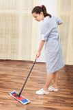 Young maid cleaning floor Royalty Free Stock Photography