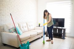 Young woman busy sweeping floor. Young maid cleaning house with broom with bucket and disinfectant kept ae near sofa Royalty Free Stock Photos