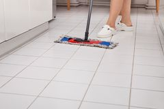 Young Maid Cleaning Kitchen Floor Stock Photos
