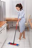 Young maid cleaning kitchen floor Royalty Free Stock Photos