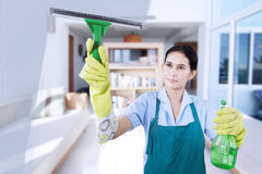 Young maid cleaning the mirror Stock Photography