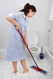 Young maid cleaning toilet Royalty Free Stock Images