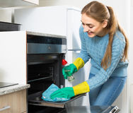 Young maid doing oven clean-up Stock Photography