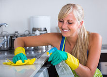Young maid dusting kitchen tops Stock Images