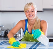 Young maid dusting kitchen tops royalty free stock photos