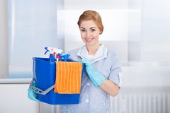 Young maid holding cleaning supplies Royalty Free Stock Images