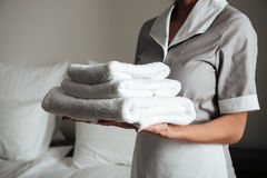 Young maid holding folded towels royalty free stock photo