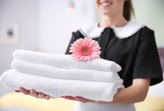 Young maid holding stack of towels and flower stock photo