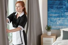 Young maid in hotel room. Cleaning service employee preparing a hotel room for a new guest royalty free stock photos
