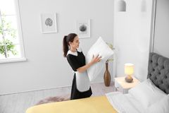 Young maid making bed. In hotel room Royalty Free Stock Photo