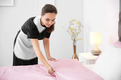 Young maid making bed. In hotel room Royalty Free Stock Photography
