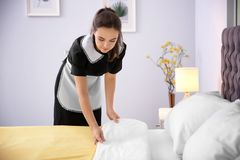 Young maid making bed. In hotel room Royalty Free Stock Photos