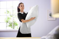 Young maid making bed. In hotel room Royalty Free Stock Image