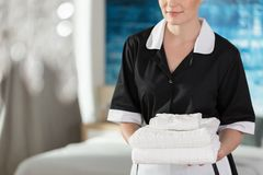 Young maid with towels. Young maid holding fresh and clean towels in a hotel room stock photos