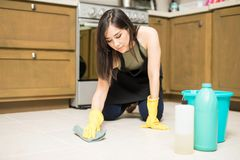 Young maid washing floor in kitchen. Pretty young woman in apron and protective gloves scrubbing tiled floor in kitchen Stock Photography