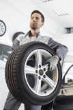Young maintenance engineer carrying tire in automobile store Stock Images