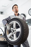 Young maintenance engineer carrying tire in automobile store Royalty Free Stock Images