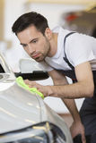 Young maintenance engineer cleaning car in repair shop Royalty Free Stock Image