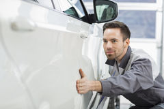 Young maintenance engineer examining car in repair shop Stock Image