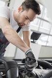 Young maintenance engineer repairing car in automobile store Royalty Free Stock Image