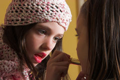 Young make-up artist. One young girl putting on make-up on another young girl Royalty Free Stock Photo
