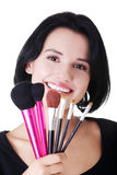 Young make-up artist woman holding brushes. Isolated on white Stock Photo