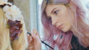 Young makeup artist applying cosmetics on model`s eyes. Royalty Free Stock Image