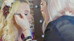Young makeup artist applying cosmetics on model`s eyes. Stock Photo