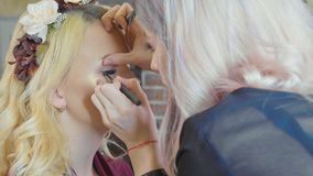 Young makeup artist applying cosmetics on model`s eyes. Royalty Free Stock Photo